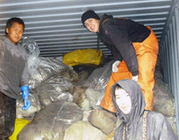 Arnold Alfred, Paul Jenson, and Clint Teeluk from the low lower Yukon River in Alaska, load collected gillnets into a container for shipping